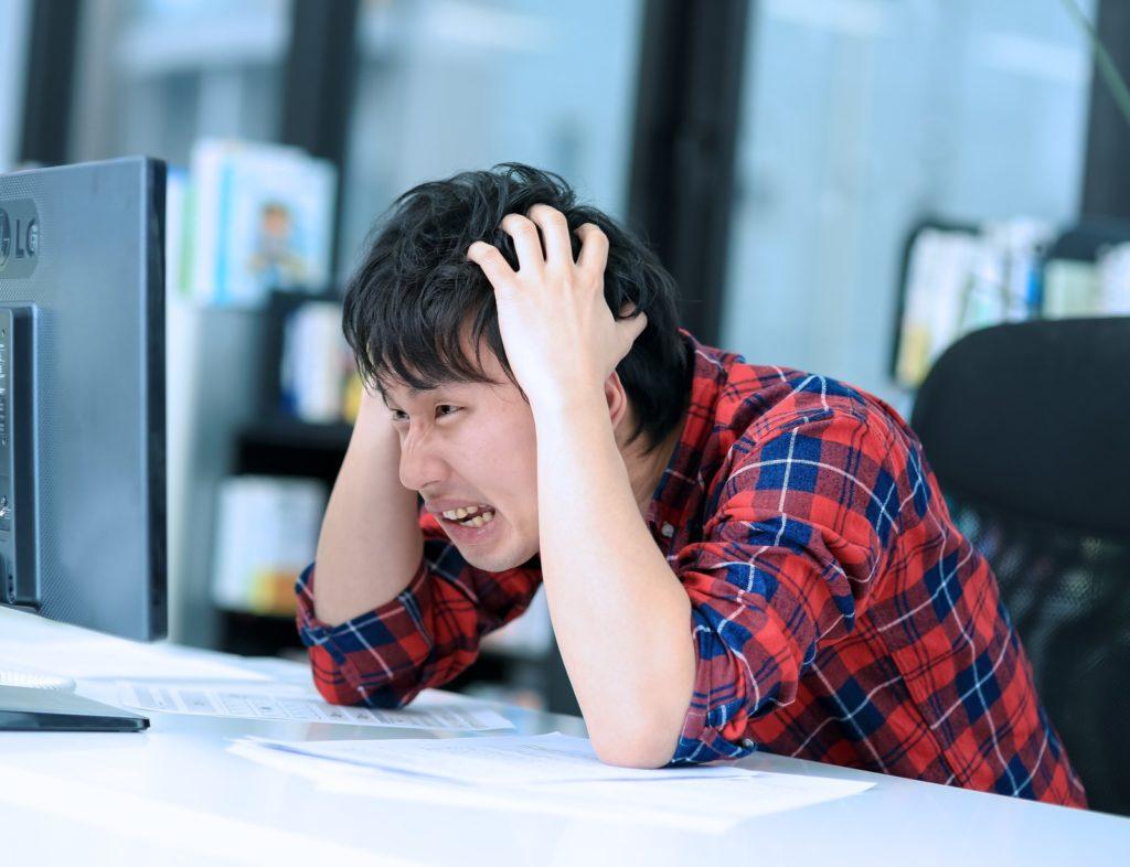 男性がパソコンの前で頭を抱えている画像