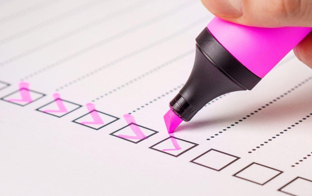チェックリストにピンクの蛍光マーカーでチェックをつけていっている画像