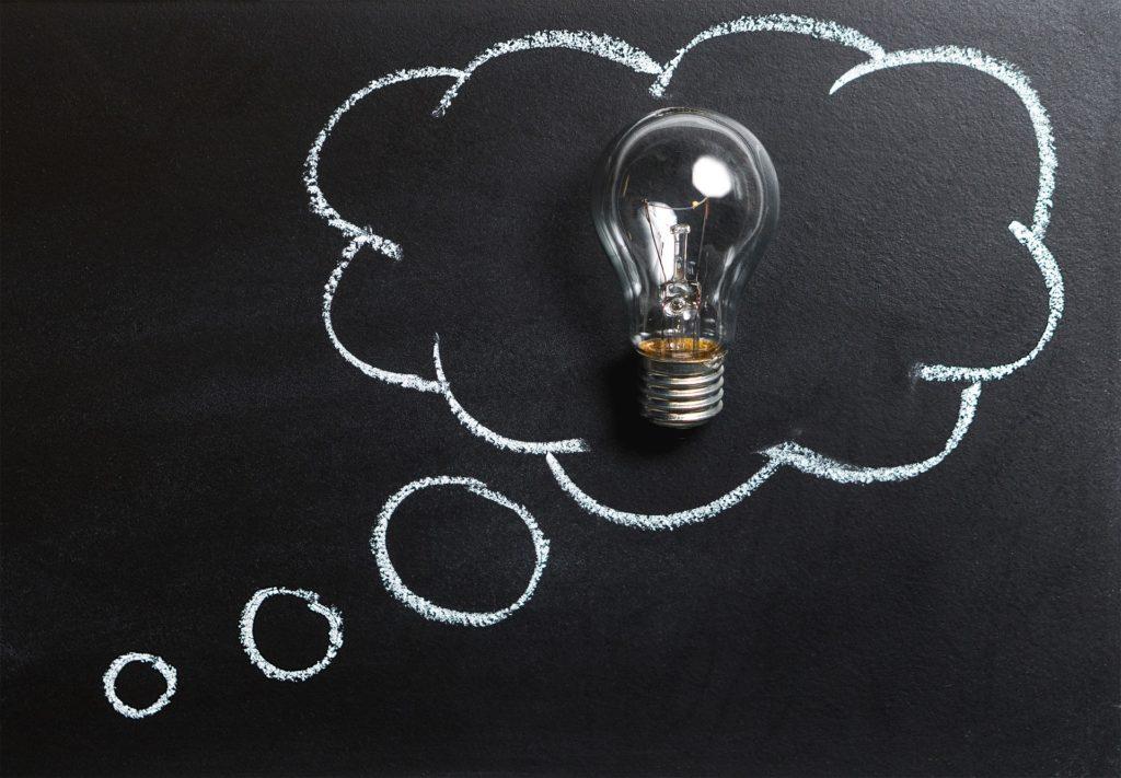 黒板にふきだしが書かれていて、その中に電球が置かれている画像