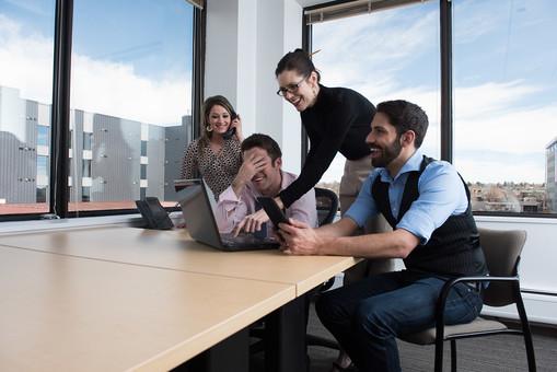男性2人と女性2人がパソコンを見ながら談笑している画像