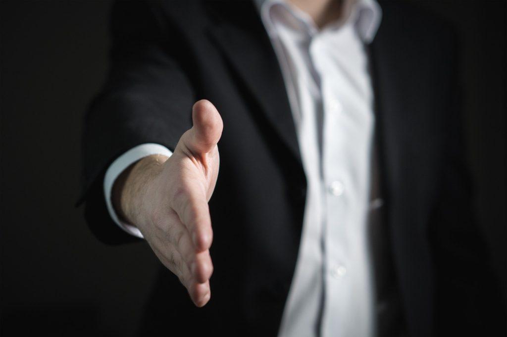 男性が手を差し出し握手を求めている画像